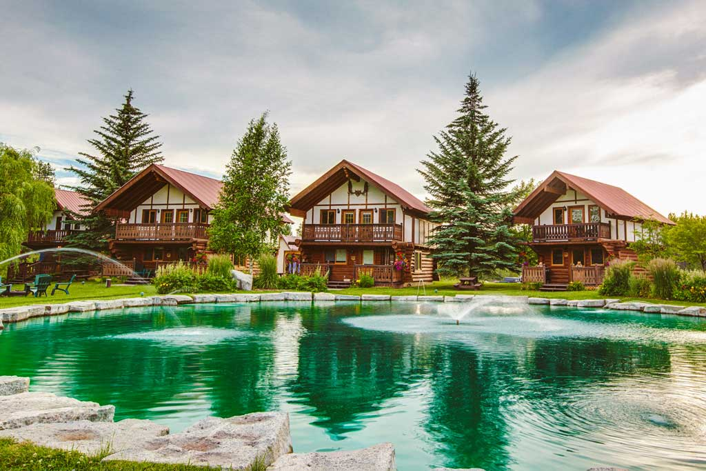 Main cabins at Great Northern Resort surrounded by tall evergreens with a water feature in front.