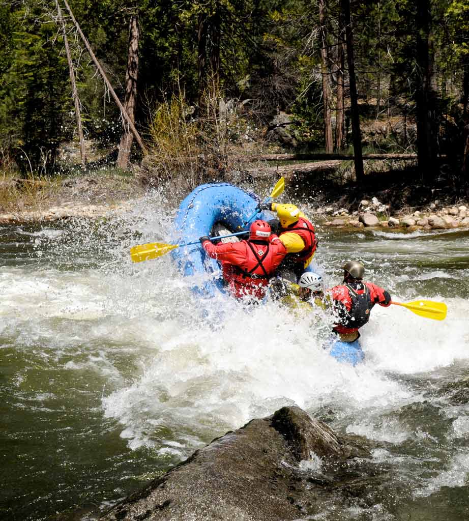 Two people on a raft hitting some turbulent waters.