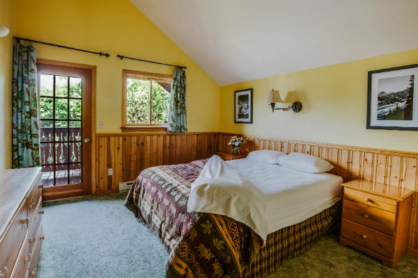 ID: A Photograph of a queen-sized bed with plaid blankets in a yellow and wood-paneled room. There is a door in the room that goes out to a deck. End ID
