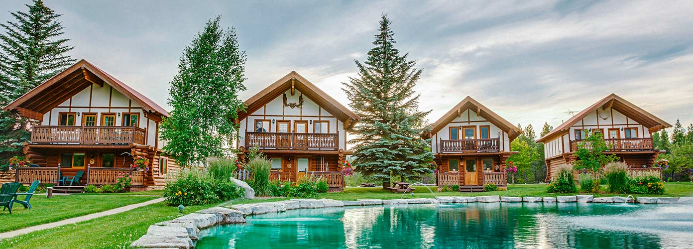 Main cabins at Great Northern Resort surrounded by tall evergreen trees with a water feature in front.